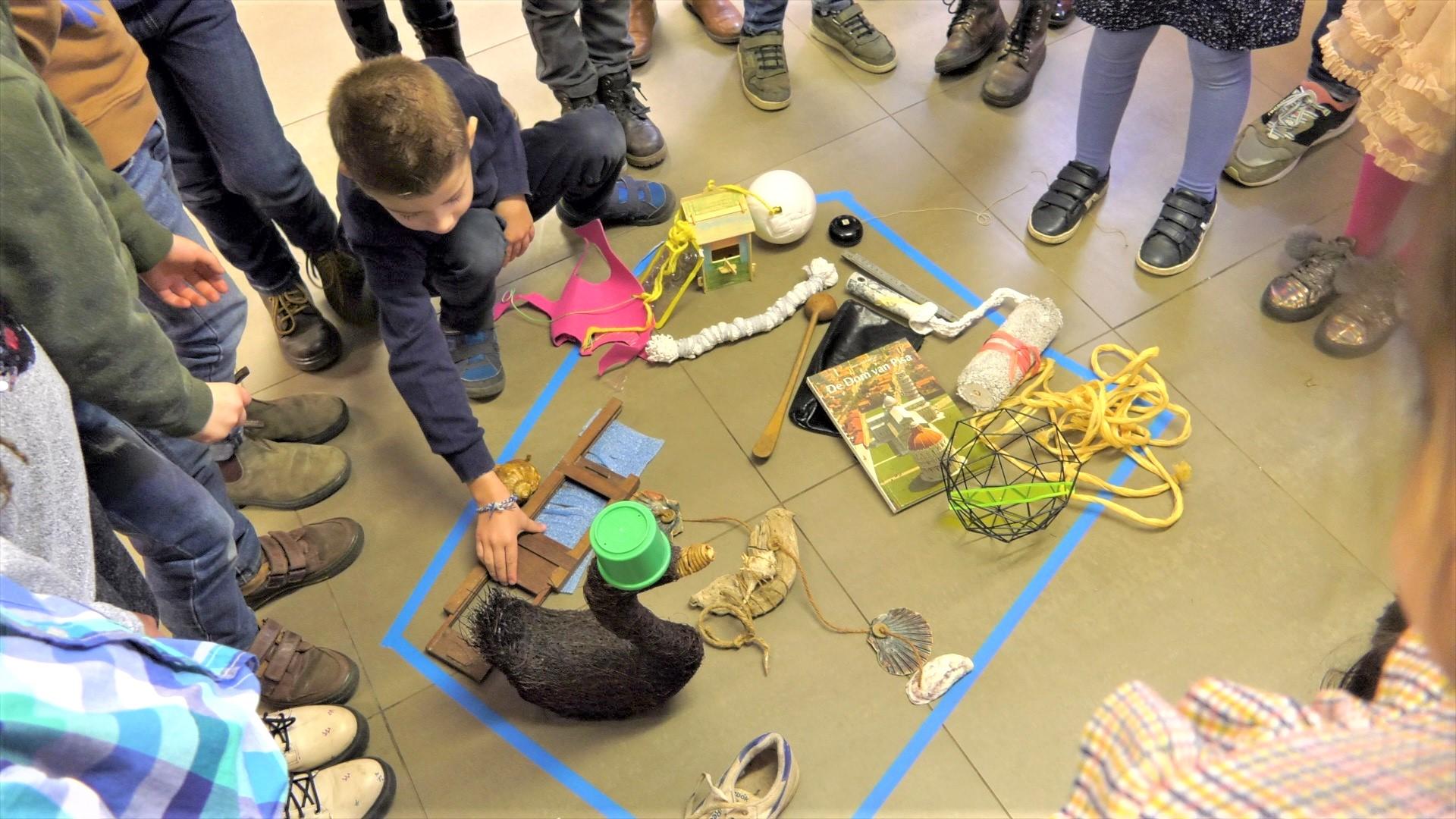 Kinderen staan in een kring rond voorwerpen die op de grond liggen. Een jongetje zit gehurkt en legt een hand op een voorwerp