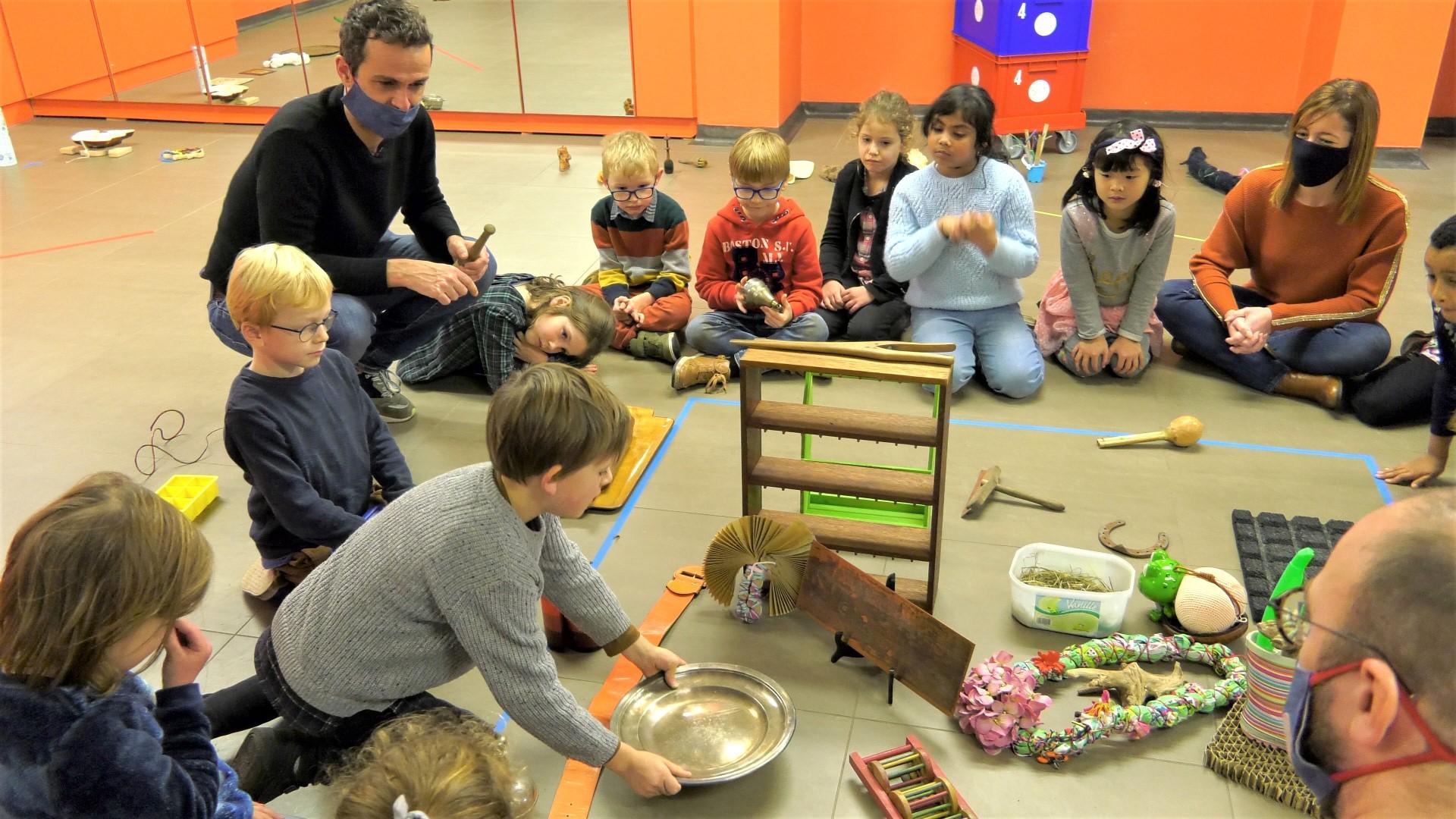 Kinderen ziten in een kring rond voorwerpen die op de grond liggen. Een jongen heeft een metalen schaal in de handen