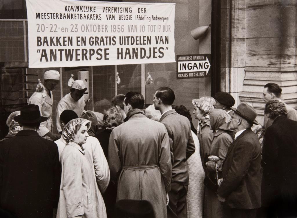 Foto: leerlingen van de bakkersopleiding INCOPA (nu PIVA) bakken Antwerpse Handjes op de Meir en delen ze gratis uit, 1956