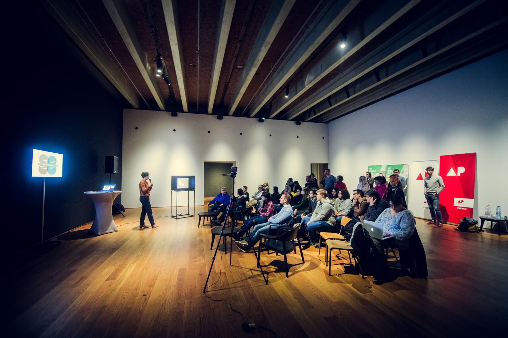 Zittend publiek luistert naar spreker vooraan in de zaal