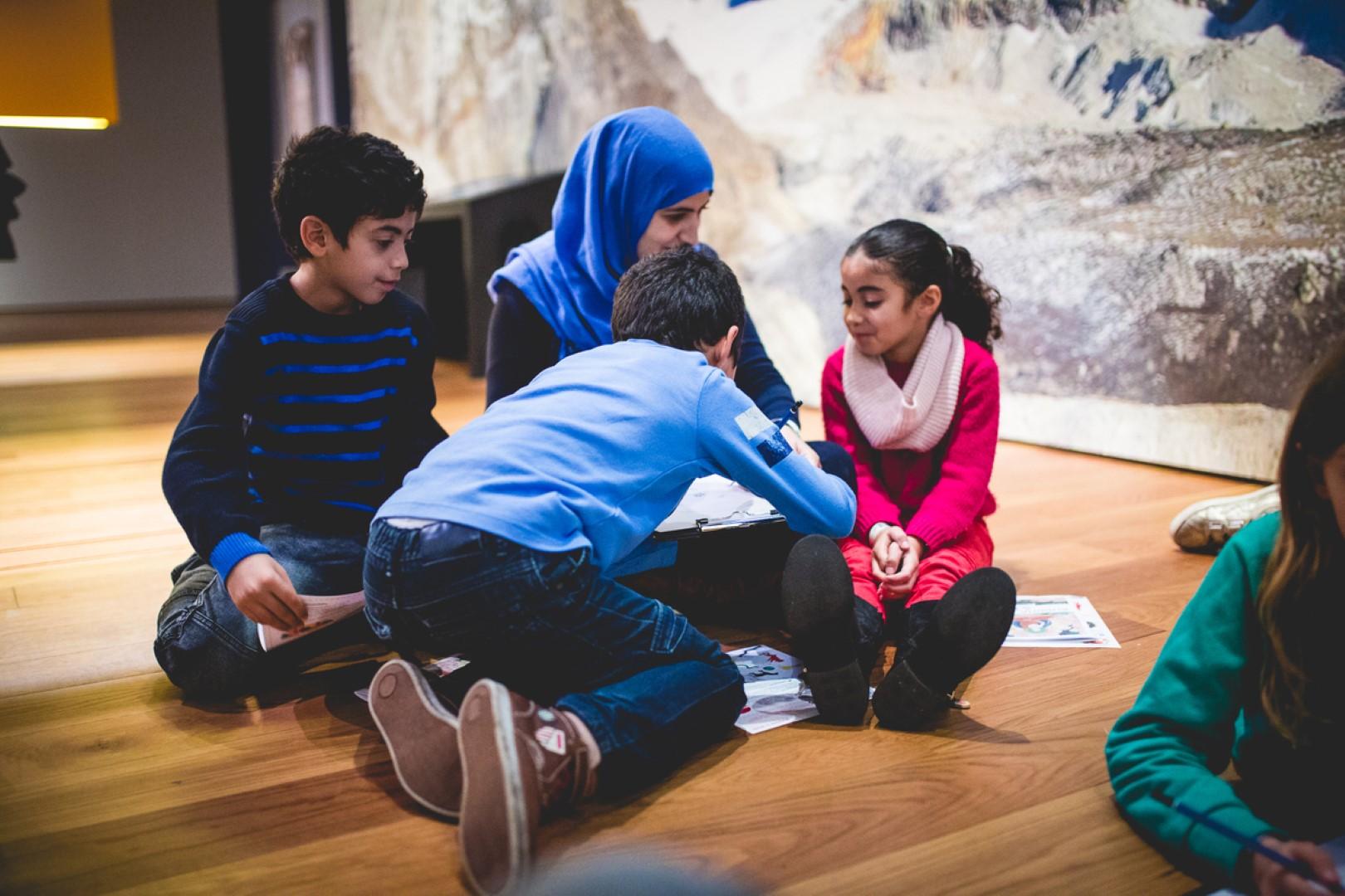 vrouw en 3 kinderen zitten op de grond