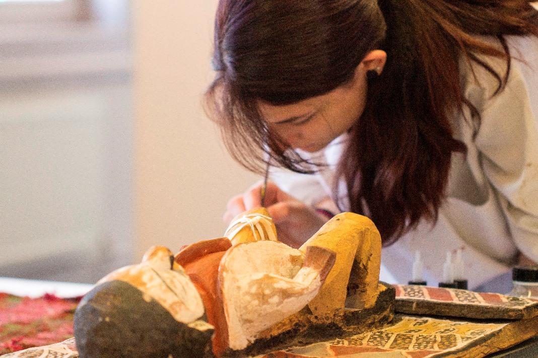 vrouw in witte schort bewerkt een houten beeld met een penseel